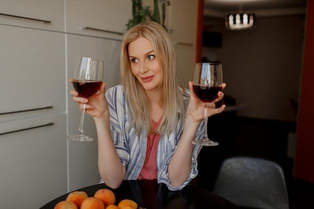 Mujer rubia prueba dos vasos de vino tinto en su propia cocina.
