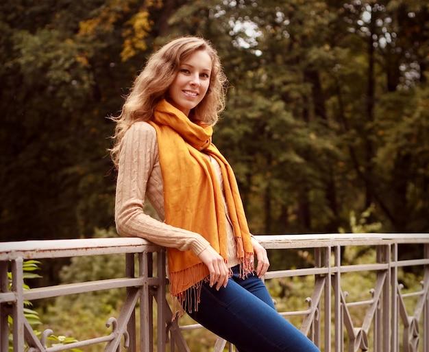 Mujer rubia en el puente en el parque otoño