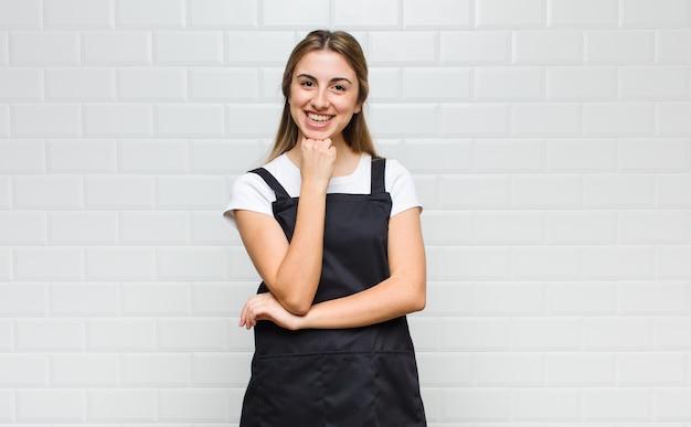 Mujer rubia que parece feliz y sonriente con la mano en la barbilla, preguntándose o haciendo una pregunta, comparando opciones
