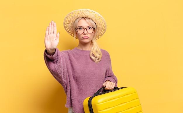 Mujer rubia que parece seria, severa, disgustada y enojada mostrando la palma abierta haciendo gesto de parada