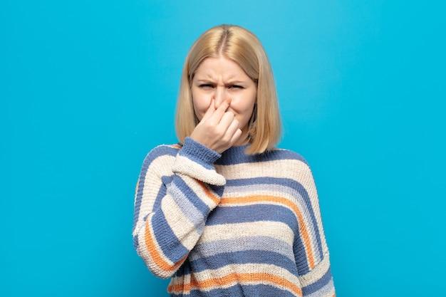 Mujer rubia que se siente disgustada, tapándose la nariz para evitar oler un hedor desagradable y desagradable