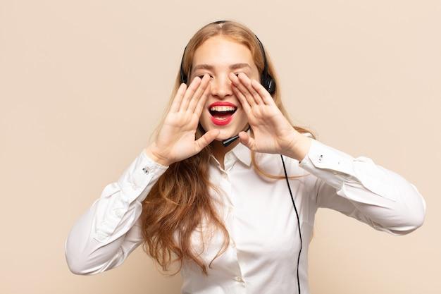 Mujer rubia que se siente feliz, emocionada y positiva, dando un gran grito con las manos al lado de la boca, gritando