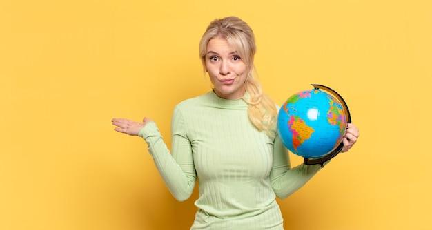 Mujer rubia que se siente perpleja y confundida, dudando, ponderando o eligiendo diferentes opciones con expresión divertida