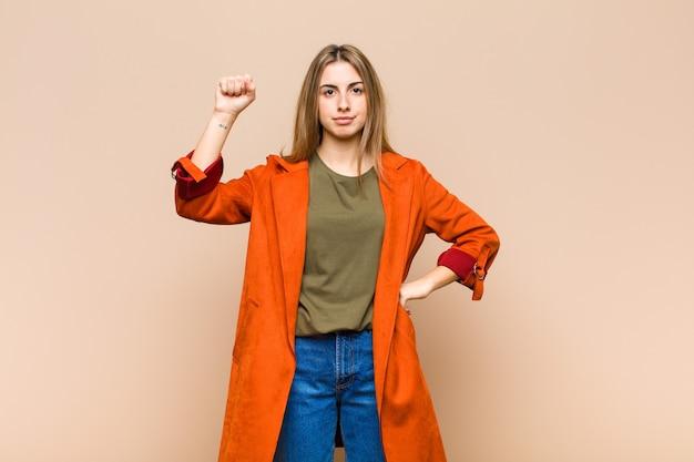 Mujer rubia que se siente seria, fuerte y rebelde, levanta el puño, protesta o lucha por la revolución