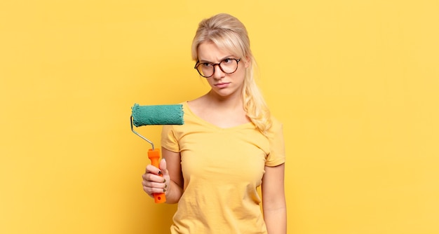 Mujer rubia que se siente triste, molesta o enojada y mira hacia un lado con una actitud negativa, frunciendo el ceño en desacuerdo