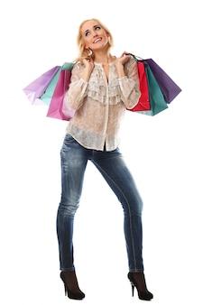 Mujer rubia que sostiene bolsos de compras