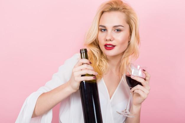 Mujer rubia que sostiene la botella de vino y el vidrio