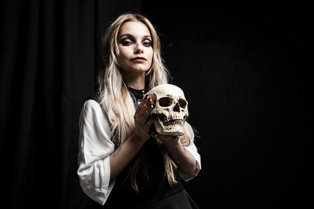 Mujer rubia que sostiene el cráneo en fondo negro