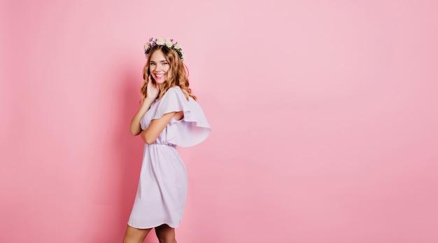 Mujer rubia refinada en vestido de verano de pie junto a la pared rosa con sonrisa