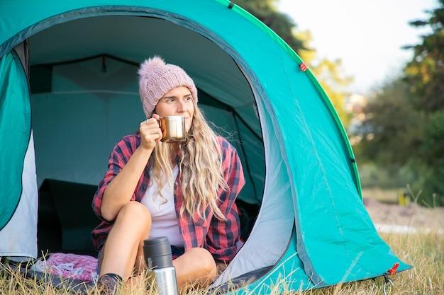 Mujer rubia relajada con sombrero bebiendo té, sentada en la tienda y mirando a otro lado. turista de pelo largo caucásico sentado en el césped. concepto de turismo, aventura y vacaciones de verano.