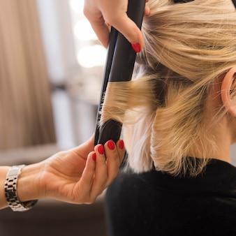 Mujer rubia rizándose el pelo
