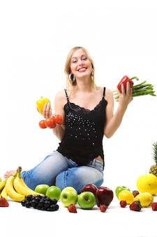 Mujer rubia rodeada de frutas y hortalizas frescas
