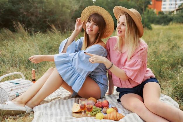 Mujer rubia romántica con su mejor amiga disfrutando de un picnic en el césped en el jardín soleado de verano.