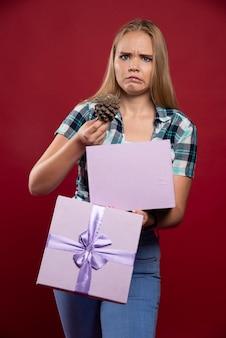 Mujer rubia saca un cono de roble de la caja de regalo y parece insatisfecha.