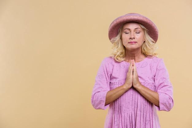 Mujer rubia senior con sombrero rosa rezando