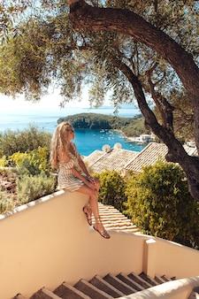 Mujer rubia sentada en las escaleras con impresionantes vistas al mar detrás