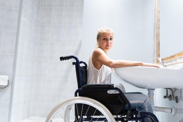Mujer rubia sentada en una silla de ruedas frente a un lavabo en un baño