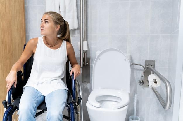 Mujer rubia sentada en una silla de ruedas junto a un baño