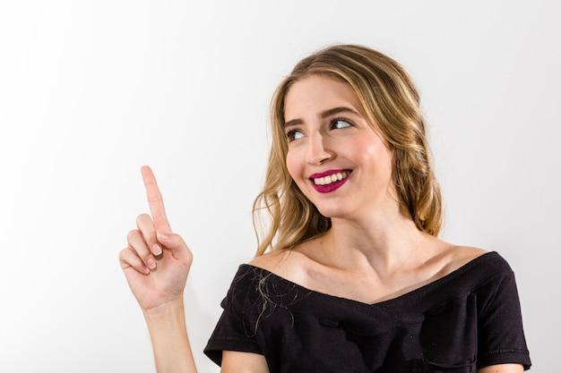 Mujer rubia sobre fondo gris que señala el dedo al lado
