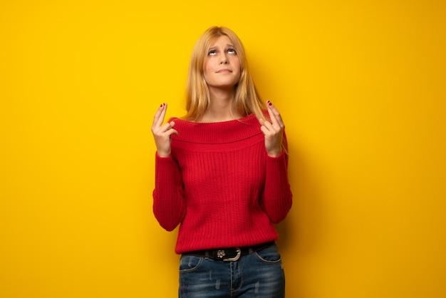 Mujer rubia sobre pared amarilla con dedos cruzándose y deseando lo mejor
