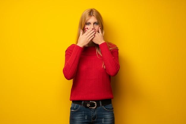 Mujer rubia sobre pared amarilla que cubre la boca con las manos por decir algo inapropiado