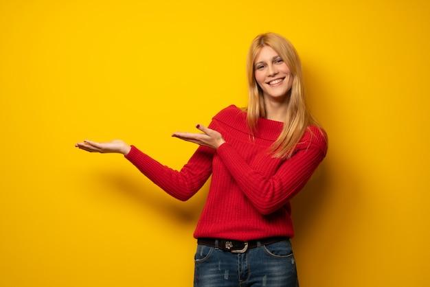 Mujer rubia sobre una pared amarilla que extiende las manos hacia un lado para invitar a venir