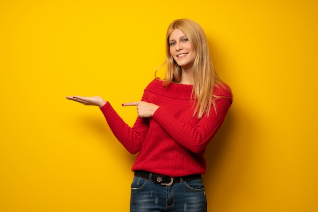 Mujer rubia sobre pared amarilla sosteniendo copyspace imaginario