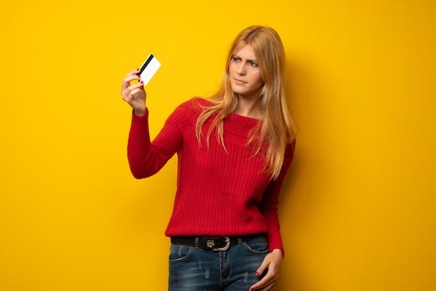 Mujer rubia sobre pared amarilla con teléfono inteligente roto con problemas