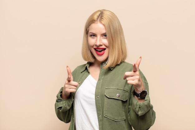 Mujer rubia sonriendo con una actitud positiva, exitosa y feliz apuntando a la cámara, haciendo un signo de pistola con las manos