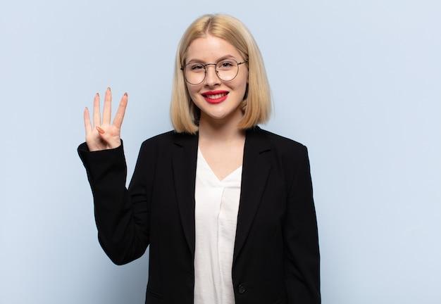 Mujer rubia sonriendo y mirando amistosamente, mostrando el número cuatro o cuarto con la mano hacia adelante, contando hacia atrás