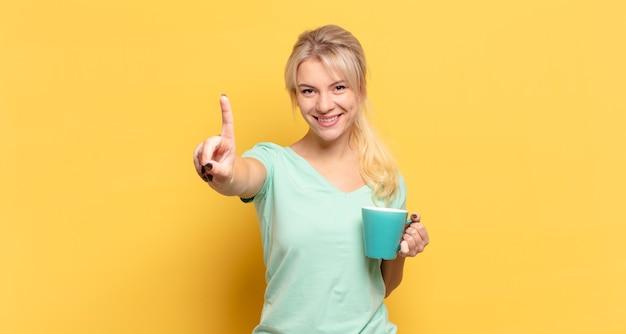 Mujer rubia sonriendo y mirando amistosamente, mostrando el número uno o el primero con la mano hacia adelante, contando hacia atrás