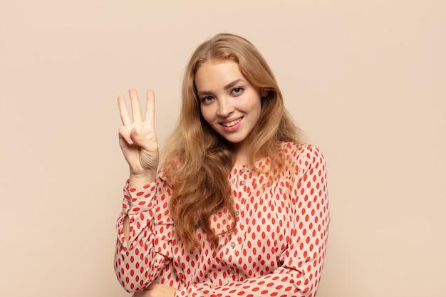 Mujer rubia sonriendo y mirando amistosamente, mostrando el número tres o tercero con la mano hacia adelante, contando hacia atrás