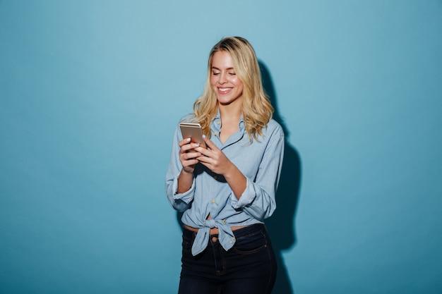 Mujer rubia sonriente en camisa escribiendo mensaje en teléfono inteligente