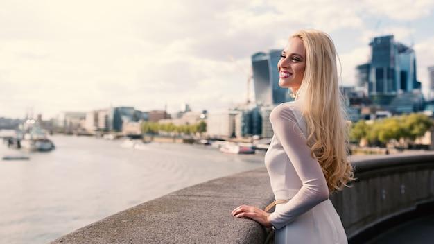 Mujer rubia sonriente con el horizonte de londres