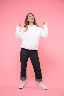 Mujer rubia sonriente de longitud completa con ropa casual apuntando y mirando hacia arriba sobre la pared rosa