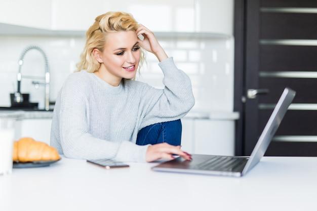 Mujer rubia sonriente que desayuna y que usa su computadora portátil en la cocina