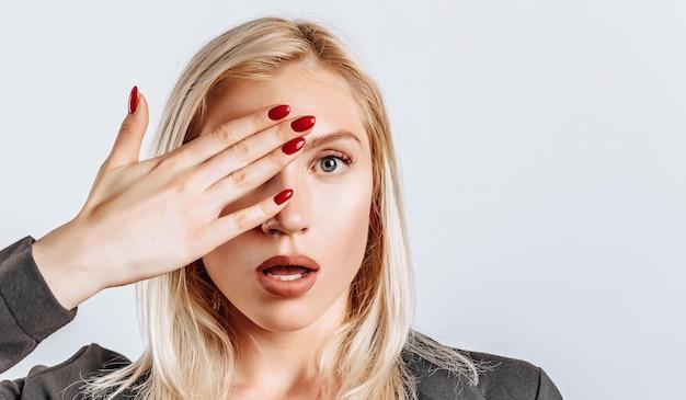 La mujer rubia se sorprende mal cubre la mitad de su rostro en un blanco