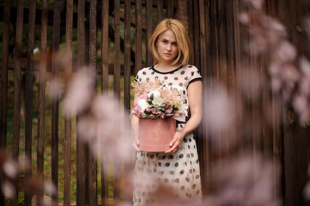 Mujer rubia sosteniendo una caja de flores de pie en el fondo de la valla de madera y el árbol floreciente rosado