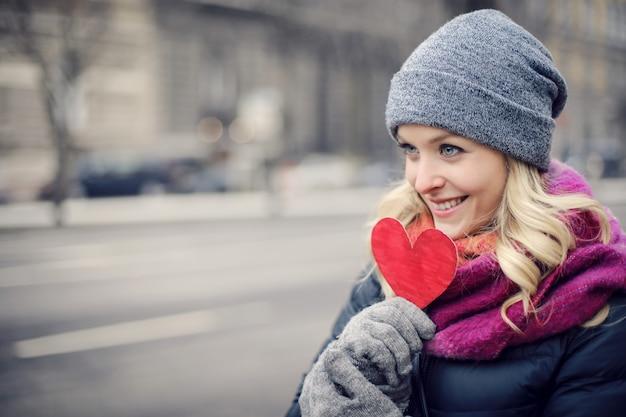 Mujer rubia sosteniendo un corazón de papel