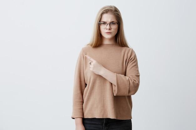 Mujer rubia en suéter marrón y anteojos apuntando con el dedo a la pared en blanco con copia espacio para texto o anuncio de producto, mirando a la cámara con expresión seria. concepto de publicidad