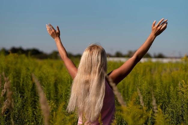 Mujer rubia con sus brazos en el aire