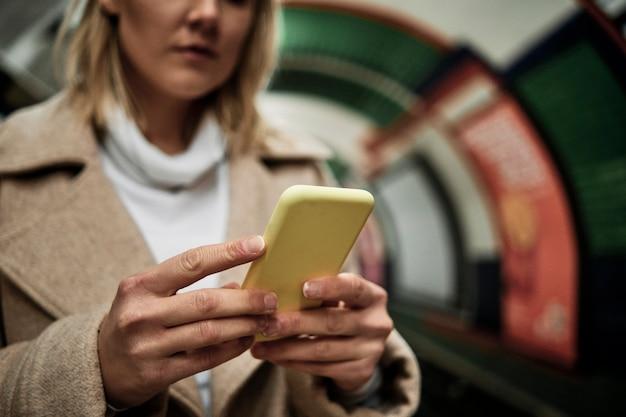 Mujer rubia con un teléfono móvil en la estación de metro de londres.