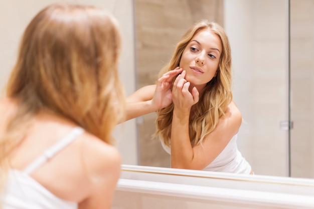 Mujer rubia tiene problemas con la piel de la cara.