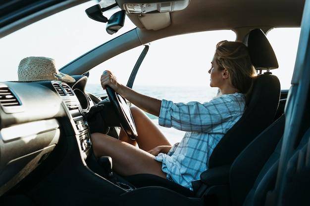 Mujer rubia de tiro medio en el asiento del conductor