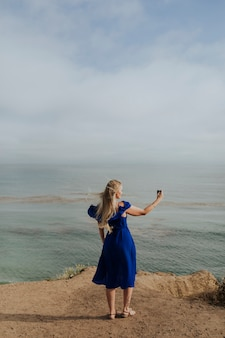 Mujer rubia tomando una foto con su teléfono