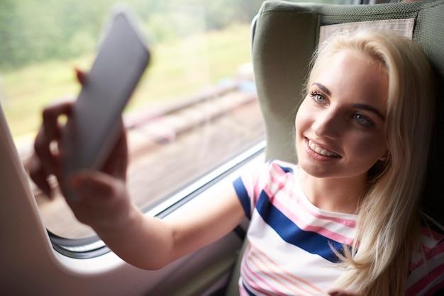 Mujer rubia tomando selfie en el tren