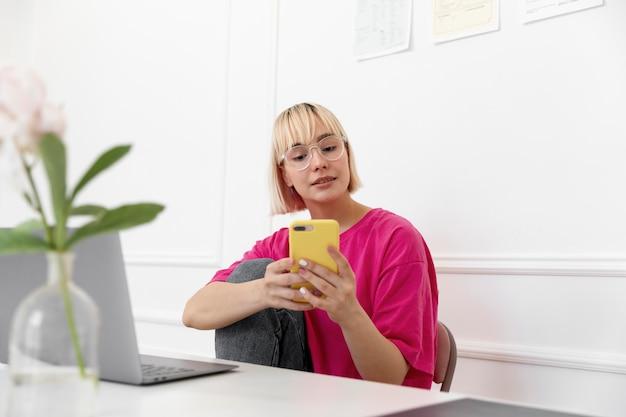 Mujer rubia trabajando desde casa en su computadora portátil