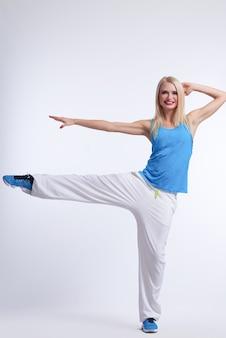 Mujer rubia en traje de baile hip hop equilibrado en una pierna sonriendo en blanco