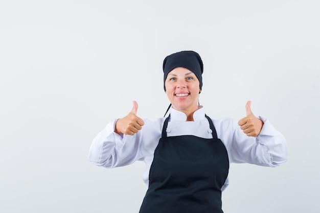 Mujer rubia en uniforme de cocinero negro mostrando doble pulgar hacia arriba y luciendo bonita