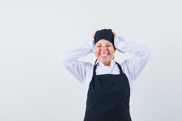 Mujer rubia en uniforme de cocinero negro presionando las manos en la oreja, cerrando los ojos y luciendo bonita